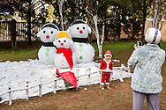 A young vietnamese kid poses in front of a fake snowman, Cock Church, Da Lat, Vietnam, Southeast Asia