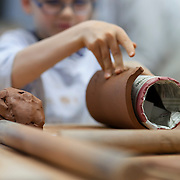 A boy working on clay during a pottery workshop
