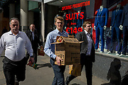 City workers walk past a new menswear retailer in the Square Mile, the capitals financial district, selling suits from £149, on 3rd March 2017, in the City of London, England.