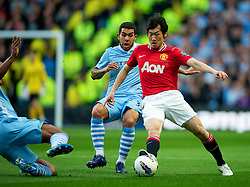 MANCHESTER, ENGLAND - Monday, April 30, 2012: Manchester City's Carlos Tevez in action against Manchester United's Park Ji-Sung during the Premiership match at the City of Manchester Stadium. (Pic by David Rawcliffe/Propaganda)