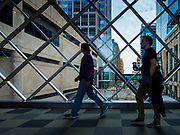 03 MAY 2017 - MINNEAPOLIS, MN: People in the skyway over 5th Street in downtown Minneapolis. The skyways are enclosed pedestrian overpasses that connect downtown buildings. The Minneapolis Skyway was started in the early 1960s as a response to covered shopping malls in the suburbs that were drawing shoppers out of the downtown area. The system grew sporadically until 1974, when the construction of the IDS Center and its center atrium, called the Crystal Court, served as a hub for the downtown skyway system. There are 8 miles of skyways, connecting most of the downtown buildings from Target Field (home of the Minnesota Twins) to US Bank Stadium (home of the Minnesota Vikings). In the last five years many upscale downtown apartment buildings and condominium developments have been added to the system, allowing downtown residents to live and work downtown without going outside.    PHOTO BY JACK KURTZ