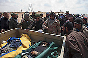 Mcc0030300 . Daily Telegraph..Rebel fighters gather around the bodies of two of their dead on the road to Brega about 50kms from Ajdabiyah. Brega is still in the control of Gaddafi's army but the rebels appear to be better organised today and gaining ground with reports of fighting around the University...Brega 1 April 2011