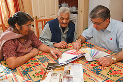 Elderly south Asian parents and son looking at colour charts.