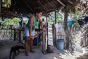 Aurideia Brito pumps water to prepare breakfast in her house in the Queimada dos Britos. Even during the harsh summers, they can pump water making it possible to live surrounded by desert. In Queimada dos Britos around 60 people live, but the locals are not sure, since there is always someone going away or coming back. They live of fishing, which is two hours away. In the winter they breed fish on the lagoons, and cattle and goats that run free on the dunes. They have a small garden for farming but nothing major since they are afraid of the accelerating advance of the dunes that have already covered several houses. No one really knows when the village was founded but the legend says that the founder Manuel Brito, when running away from home due to a drought that was scorching his homeland, he ended up settling down in the only non-sandy portion of the Lençois.