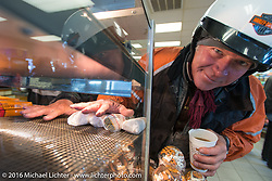 Dean Bordigioni has his hands in the burrito warmer at the first gas stop on this 39 degree (27 degree windchill) morning during Stage 14 - (284 miles) of the Motorcycle Cannonball Cross-Country Endurance Run, which on this day ran from Meridian to Lewiston, Idaho, USA. Friday, September 19, 2014.  Photography ©2014 Michael Lichter.