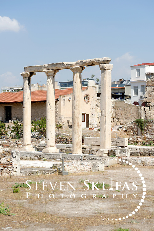 Athens. Greece View of four standing columns which stand on the original inner peristyled courtyard atrium of Roman Emperor Hadrian's lavish Library built in 131 AD in Athens. Occupying the courtyard from 425 AD was a monumental Tetraconch Christian church which was then replaced by a 7th century church of which standing columns survive. The library complex consisted of a vast library, a large courtyard with a garden and central pool, mosaics floors, numerous rooms and a facade adorned with Corinthian columns.