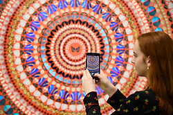 """Licensed to London News Pictures. 19/09/2019. LONDON, UK.  A staff member poses with a smartphone next to """"Deity"""", 2019, by Damien Hirst.  Preview of a new exhibition by Damien Hirst at White Cube's Mason's Yard gallery in Mayfair.  It is the artists first major solo exhibition in seven years and features large-scale concentric butterfly paintings from his new """"Mandalas"""" series.  22 large scale works are on display 20 September to 2 November 2019..  Photo credit: Stephen Chung/LNP"""