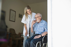 Nurse with senior man on wheelchair drinking a glass of juice in rest home, Bavaria, Germany, Europe