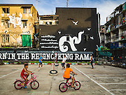 """01 DECEMBER 2016 0 BANGKOK, THAILAND: Boys ride their bikes around the takraw court in Chalermla Park (Graffiti Park) in Bangkok. The east wall of the park was repainted with a large mural that says """"Born in the reign of King Rama 9,"""" with the nine written in Thai script. Bhumibol Adulyadej, the Late King of Thailand, was known as Rama 9. The park was repainted in his honor after his death on Oct 13.    PHOTO BY JACK KURTZ"""