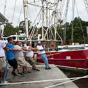 SNEADS FERRY, NC - SEPTEMBER 13,  2018:  Crew members and boat owners help to moor Miss Janice, a shrimp boat,  to the dock at Mitchell Seafood on Wheeler Creek in Sneads Ferry, NC on September 13, 2018 in advance of Hurricane Florence.  Logan Cyrus for AFP