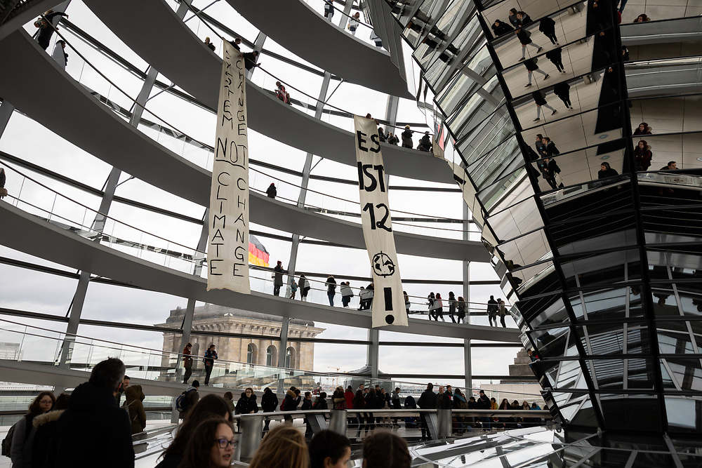 """Aktivisten von Youmove protestieren mit Bannern mit Aufschriften wie """"Fridays for Future"""", """"You move - Globale Jugendbewegung"""", """"System change not climate change"""" und """"Es ist fünf vor Zwölf"""" in der Reichstagskuppel über dem Bundestag für mehr Klimaschutz. Sie fordern, die Vereinbarungen des Pariser Klimaabkommens einzuhalten und die Erderwärmung auf 1,5 Grad zu begrenzen.<br /> <br /> [© Christian Mang - Veroeffentlichung nur gg. Honorar (zzgl. MwSt.), Urhebervermerk und Beleg. Nur für redaktionelle Nutzung - Publication only with licence fee payment, copyright notice and voucher copy. For editorial use only - No model release. No property release. Kontakt: mail@christianmang.com.]"""