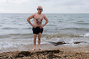 A tired and cold sea swimmer pauses after emerging from the tidal waters of the Thames Estuary, on 25th July 2021, in Whitstable, England.