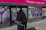 An elderly Czech lady in the Holesovice district walks past shop posters showing dance and exercise classes at a local gym in Prague 7, on 20th March, 2018, in Prague, the Czech Republic.