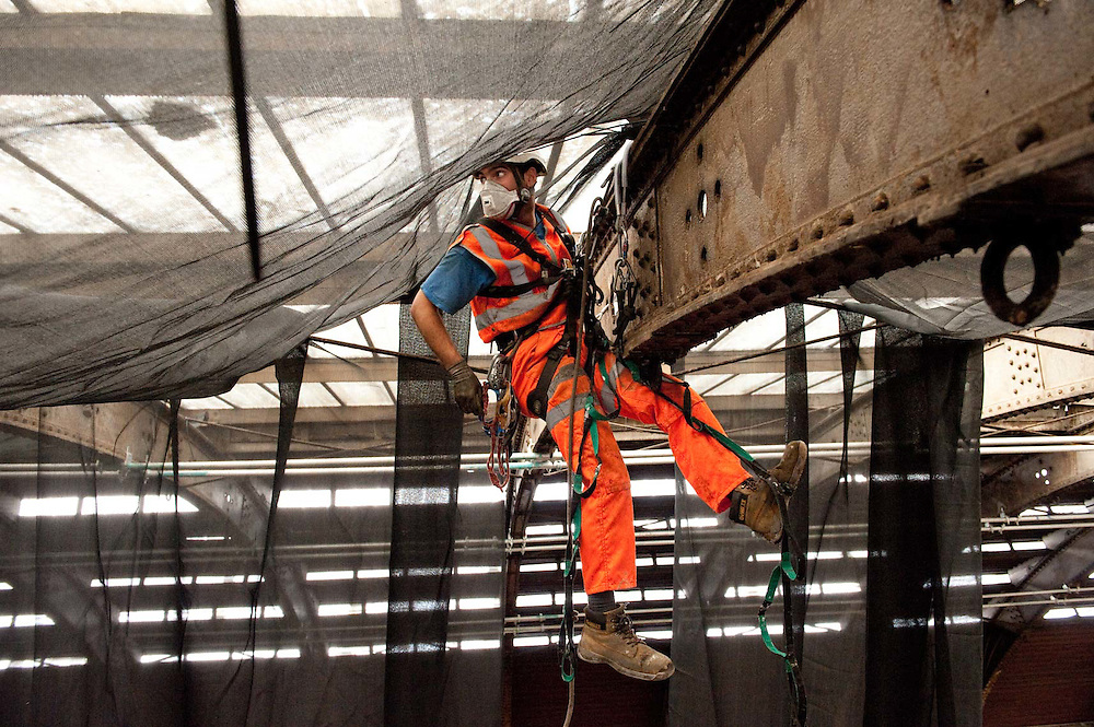 Rope access workers fitting safety netting, Paddington Station, London.
