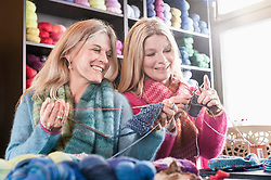 Two women knitting muffler in coffee shop and smiling, Bavaria, Germany