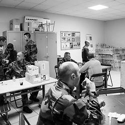 """jeudi 20 octobre 2016, 05h45, Versailles. Dans la """"popote"""" du bâtiment certains soldats du 511ème Régiment du Train déjeunent en regardant la télévision. Comme la majorité des soldats fait le choix de déjeuner à l'arrivée à la vigie de son lieu de patrouille, des cartons avec les éléments du petit-dej sont prêts à être embarqués."""