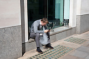 Office worker taking a break vaping while staring at his smart phone on the street in London, England, United Kingdom. Vaping is often seen as a safe or safer alternative to smoking. It is also relatively new to the market, only hitting the mainstream over the past decade or so.