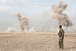 © Licensed to London News Pictures. 30/09/2015. Kirkuk, Iraq. A Kurdish peshmerga fighter watches the smoke plumes from two large bombs dropped by coalition air support to suppress ISIS positions in the village of Mansoria during an offensive aimed at capturing 11 villages from the Islamic State near Kirkuk, Iraq.<br /> <br /> Supported by large amounts of coalition airstrikes, members of the Iraqi-Kurdish peshmerga today (30/09/2015) took part in an offensive to take seven villages across a large front near Kirkuk, Iraq. By mid afternoon the Kurds had reached most of their objectives, but suffered around 10 casualties all to improvised explosive devices. All seven villages were originally Kurdish and settled with other ethnic groups during the Iraqi Arabisation process of the 1970's and 80's. Photo credit: Matt Cetti-Roberts/LNP