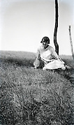 young adult sitting in grass field 1920s
