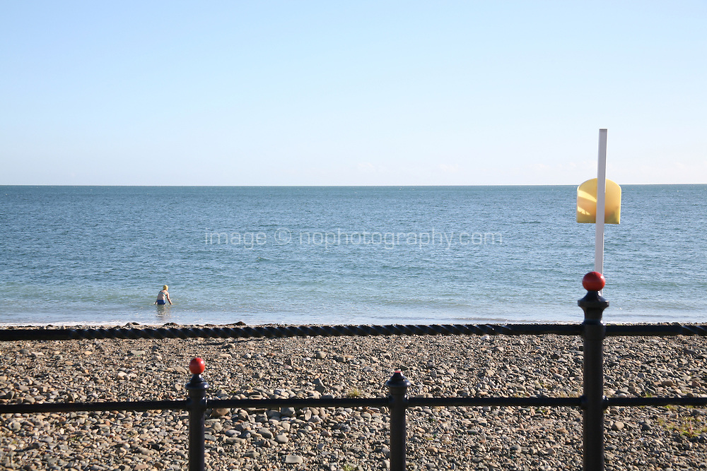 Woman swimming at the pebble beach at Bray County Wicklow Ireland
