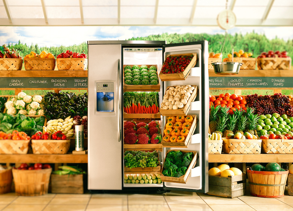 A General Electric refrigerator photographed inside of a studio set built to replicate a produce market.