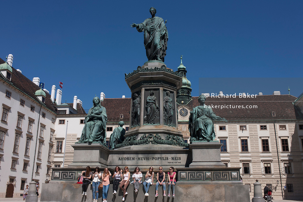Young women sit beneath the monument to Emperor Franz Josef 2nd in the courtyard of the Hofburg Kaiserappartements in Vienna, Austria, EU.