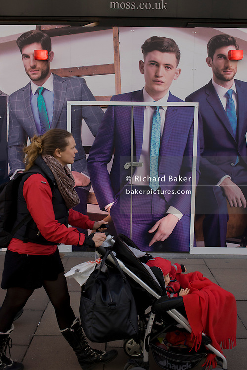 Construction hoarding featuring suited young men for dress hire business Moss Bros in central London.