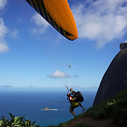 A tandem para glider takes off from the hillside of Pedro Bonita high in the hills of Rio de Janeiro. Pilots of hang gliders and para gliders take tourists for tandem flights with breathtaking views of the city before landing on Sao Conrado beach. Rio de Janeiro,  Brazil. 9th September 2010. Photo Tim Clayton