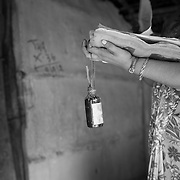 A vaccinator holding a bottle of red paint used for house marking at a village on the flood plains of the Kosi river near Kusheshwar Asthan (E), Bihar.