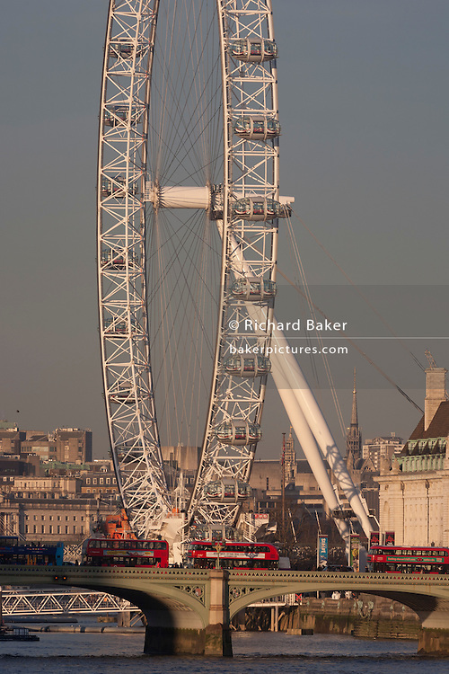 The London Eye, the UK's top tourist attraction, rises above buses and traffic crossing Westminster Bridge and the River Thames, on 18th January 2017, in London England.