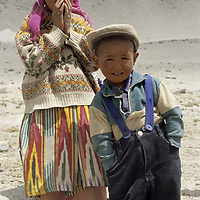 A nomadic Kygyz boy and his sister pose shyly near the summer home in the Pamir Mountains of Xinjiang China.