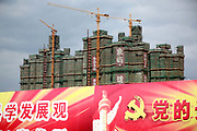New apartment building developments seen standing behind propaganda for the Chinese Communist Party in Kunshan, Jiangsu Province, China on 25 October, 2011. As China's central government shows no intention to loosen its policy restrictions on the housing market despite 4 consecutive  months of price drops,  local governments must find a way to repay the 10.7 trillion yuan ($1.7 trillion) in debt as their land sale revenue dropped 13 percent from the previous year and with no end in sight.