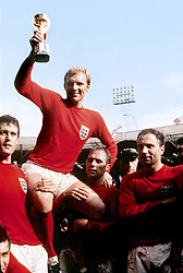 England captain Bobby Moore displays the World Cup trophy whilst being carried by his England colleagues after their 4-2 win against West Germany.