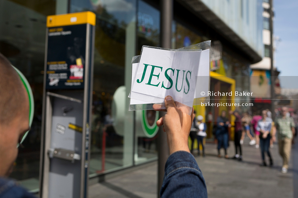 The hand of a Christian holds up a small sign with the word Jesus for tourists of many countries and cultures in Leicester Square, on 29th August 2019, in London, England.