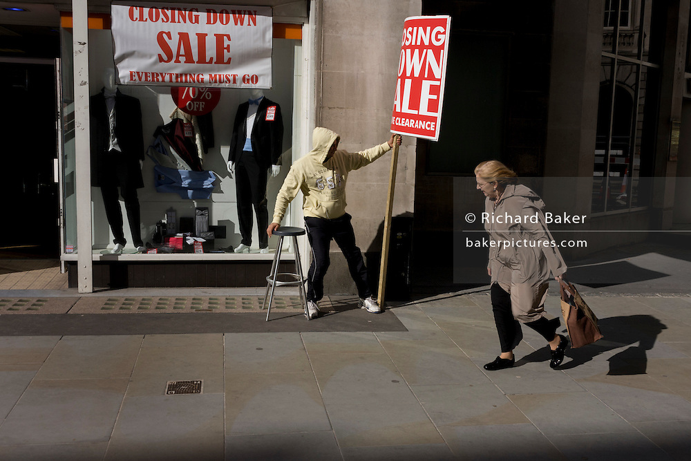 During a windy afternoon, a sandwich board man holds on to his sign for a menswear shop's closure sale in central London