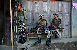 "SOLAN DISTRICT, NEPAL, APRIL 24, 2004: Royal Nepalese Army soldiers sit in a village in Solan  district April 24, 2004.The soldiers are fighting Maoist guerrillas who are trying to make Nepal a communist state. Analysts and diplomats estimate there about 15,000-20,000 hard-core fighters, including many women, backed by 50,000 ""militia"".  In their remote strongholds, they collect taxes and have set up civil administrations, and ""people's courts"" to settle rows. They also raise money by taxing villagers and foreign trekkers. Though young, they are fearsome fighters and  specialise in night attacks and hit-and-run raids. They are tough in Nepal's rugged terrain, full of thick forests and deep ravines and the 150,000 government soldiers are not enough to combat this growing movement that models itself after the Shining Path of Peru. (Ami Vitale/Getty Images)"