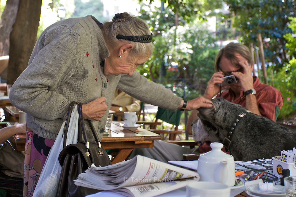 Man and old lady admire an old and very large Great Dane at a streetside cafe in Recoleta, Buenos Aires.