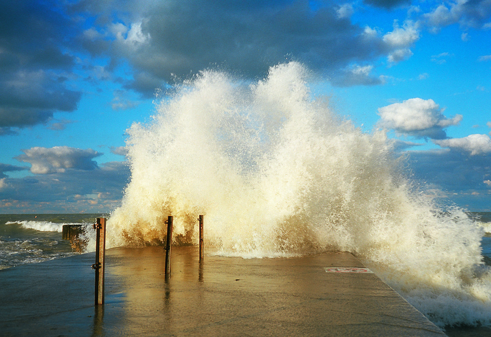 Storm over Lake Michigan produces a big splash at the end of one of many piers near Chicago