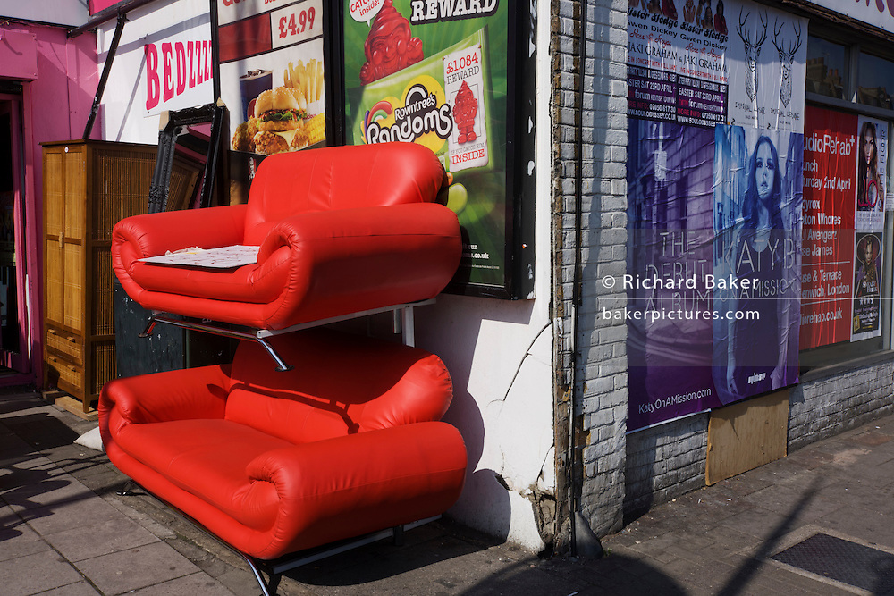 Posters and bright red sofas on sale in a London street.