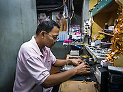 11 OCTOBER 2015 - BANGKOK, THAILAND: A man repairs electronic game controllers in his shop in the Saphan Lek market on what the Bangkok city government is saying was the last day of business for the market. Many shops in the market are already closed. Street vendors and illegal market vendors in the Saphan Lek area will be removed in the next two weeks as a part of an urban renewal project coordinated by the Bangkok Metropolitan Administration. About 500 vendors along Damrongsathit Bridge, popularly known as Saphan Lek, have until Monday, October 11,  to relocate. Vendors who don't move will be evicted. Saphan Lek is one of several markets and street vending areas being closed in Bangkok this year. The market is known for toy and replica guns, bootleg and pirated DVDs and CDs and electronic toys.    PHOTO BY JACK KURTZ