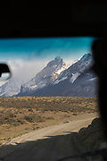 Snowcapped mountains in Torres del Paine National Park, seen through the window of a bus. Chile
