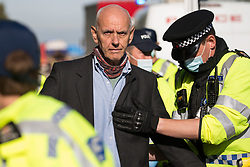 Ockham, UK. 21st September, 2021. Surrey Police officers arrest an Insulate Britain climate activist who had previously blocked the clockwise carriageway of the M25 between Junctions 9 and 10 as part of a campaign intended to push the UK government to make significant legislative change to start lowering emissions. Activists briefly halted traffic on both carriageways of the motorway before being removed and arrested by Surrey Police.