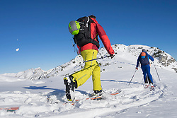 Rear view of skiers walking towards mountain