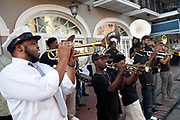 A jazz band busking, playing in the street on Bourbon Street, French Quarter, New Orleans, Louisiana, USA. walking down the street in the French Quarter,