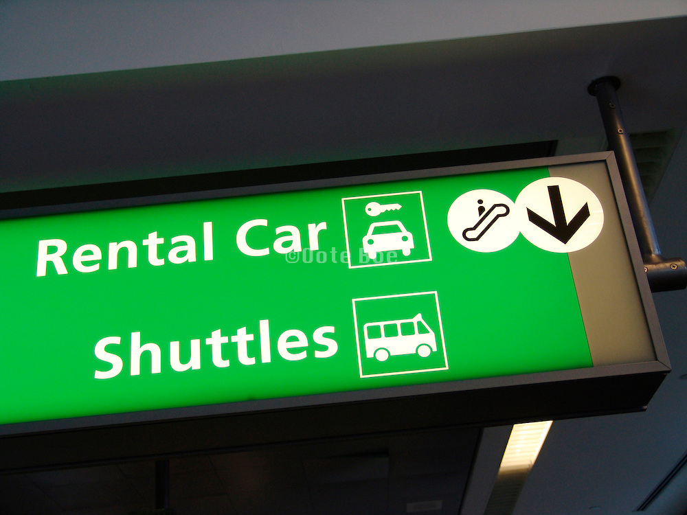 Overhead sign to public transportation and car rental office.