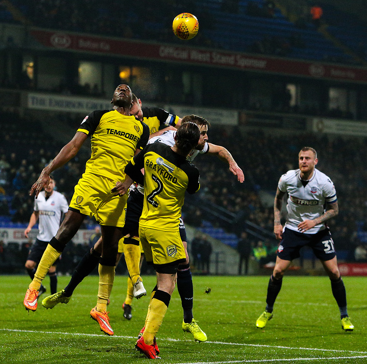 Bolton Wanderers' Mark Beevers jumps for a header with Burton Albion's Jake Buxton, Lucas Akins and John Brayford<br /> <br /> Photographer Alex Dodd/CameraSport<br /> <br /> The EFL Sky Bet Championship - Bolton Wanderers v Burton Albion - Saturday 16th December 2017 - Macron Stadium - Bolton<br /> <br /> World Copyright © 2017 CameraSport. All rights reserved. 43 Linden Ave. Countesthorpe. Leicester. England. LE8 5PG - Tel: +44 (0) 116 277 4147 - admin@camerasport.com - www.camerasport.com