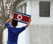 A North Korean man fixes a national flg on to a boat in the North Korea-China border town of Sunuiju, DPRK October 10, 2006.