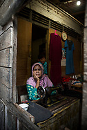 Central Kalimantan, Indonesia - March 5, 2017: At 7:30 a.m., a woman sits beside a sowing machine in her stall at the market in Kumai, Central Kalimantan, Indonesia