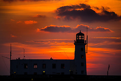 © Licensed to London News Pictures. 24/02/2018. Scarborough UK. The sun rises this morning behind the light house on St Vincent Pier in Scarborough as the UK prepares for the big freeze in the coming days. Photo credit: Andrew McCaren/LNP
