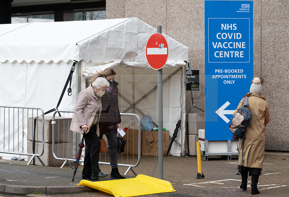 © Licensed to London News Pictures. 20/01/2021. London, UK. An elderly man and woman walk into the Olympic Office Centre, near Wembley Stadium to receive a Covid-19 vaccination jab. The hub is is one of 10 new centres inviting over 70 year olds to receive a vaccination. Photo credit: Ray Tang/LNP